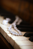 Beautiful sparkling necklace and earrings laying on piano keys - 171561442
