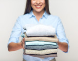 Woman holding stack of folded clothes. - 171568022