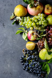 Variety of autumn fruits ripe organic apples, three kind of grapes, pears with leaves over dark texture background. Top view with space