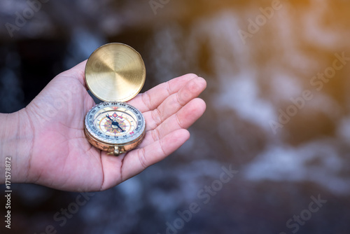 Hand is holding a compass  on waterfall background - 171578872