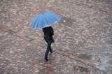 femme traversant une place pavés avec un parapluie - 171600256