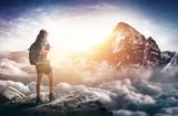 Bergsteigerin steht auf Berggipfel und genießt die Aussicht