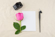Blank white card, oblique pen and bottle of ink decorated with pink rose on white muslin fabric with copy space