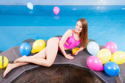 Poster Girl relaxing at swimming pool with drink