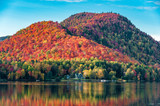 The hills covered with red maple forests behind a wooden house on the shore of a lake  in Quebec, on a beautiful autumn evening. - 171625060