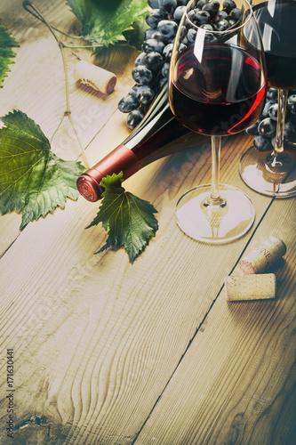 Foto Murales Два бокала красного вина  с виноградом и бутылкой на деревянном столе.