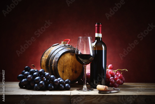 Red wine glass with bunches of grapes, bottle and small barrel