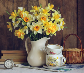 Bouquet of yellow daffodils in a white jug.