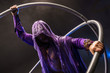 Fairy-tale character assassin in a purple cloak with a hood with two large cross wheel
