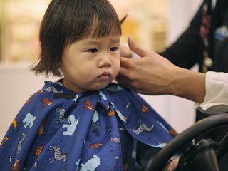 Asian baby girl do hair cut first time in hairdressing shop