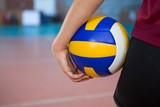 Female player holding volleyball in the court