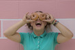 Teenage girl being silly holding two donuts over her eyes.