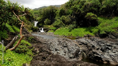 A breeze gently ruffles small trees in a small valley with a waterfall and a pond