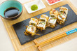 Sushi rolls on black slate surface. Japanese food. Set of sushi and maki on stone table