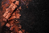 Broken chocolate pieces and cocoa powder on marble. - 171715869