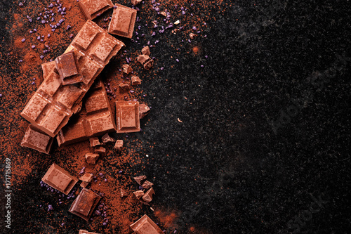 Broken chocolate pieces and cocoa powder on marble.