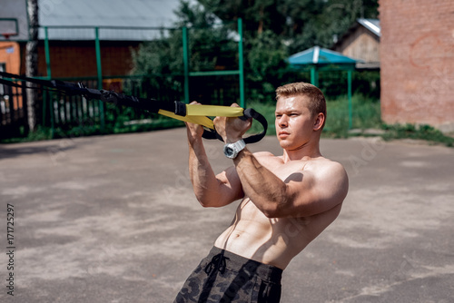 Male athlete close-up, trains nature the city, summer training loops training, Balance motivation, tanned skin in shorts. Exercise in the arms. A sunny day.