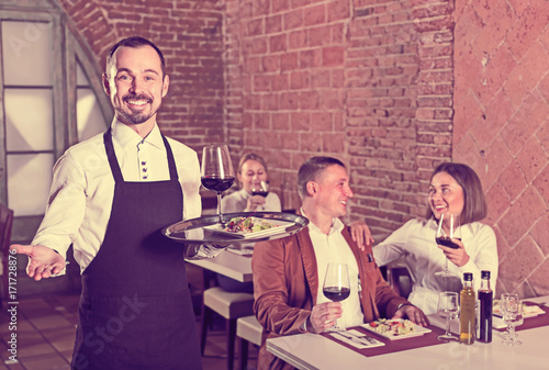 Young man waiter demonstrating country restaurant
