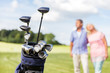 Set of golf clubs with senior couple in the background.