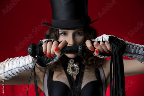 girl in a hat holds a whip in front of her face Poster