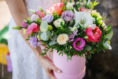 girl holding beautiful mix flower bouquet in round box