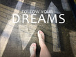 Follow your dreams word with arrow on road and woman feet background