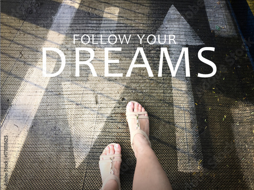 Follow your dreams word with arrow on road and woman feet background Poster
