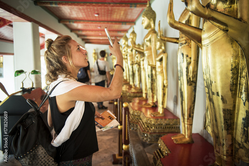 Side view of caucasian woman taking photo of Buddha statue in Thai temple Poster