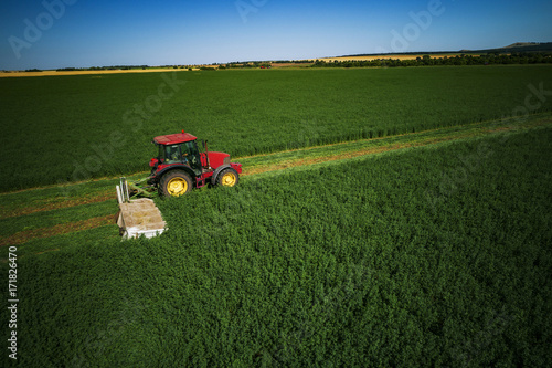 Staande foto Gras Industrial Tractor mowing green field, agriculture concept
