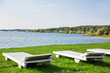 White wooden chaise lounges on the bank of the Ilyinsky reservoir. Outdoor recreation. Moscow region, Russia.