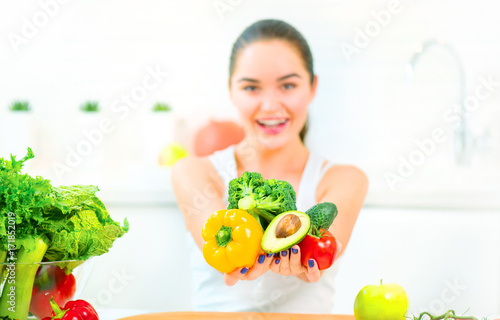 Beauty young woman holding fresh vegetables and fruits in her kitchen at home. Healthy eating concept - 171852019