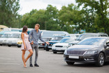 Young couple chooses used car in the street showroom.