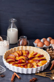Fresh ripe plums in the homemade pie, baking ingredients and kitchen utensil for cooking and baking