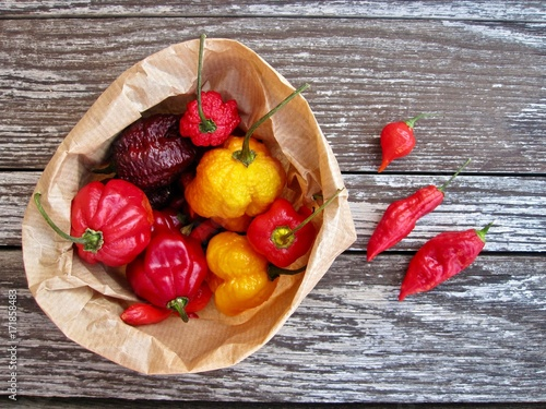 Red and yellow chillies in paper bag and on old table Poster