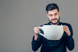 business man holding a funny huge and oversized cup of black coffee in caffeine - 171862811