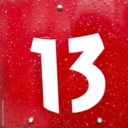 Poster White number thirteen sign on a red metal plate