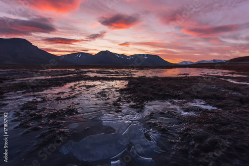 Fotobehang Zee zonsondergang Landscape travel of a nature of a sunset sunrise with clouds in the mountains of Spitsbergen Svalbard near the Norwegian city Longyearbyen