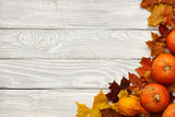 Autumn leaves and pumpkins over old wooden background - 171891674
