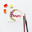 """Word """"Happy"""", watercolor cuvettes, paint brushes on a white background. Artist workspace"""