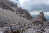 Path near giant boulders in a dark and cloudy mountain scenery, Dolomites, Cortina d'Ampezzo, Italy - 171901636