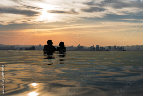 A couple at the edge of an infinity pool looking out at the city Poster