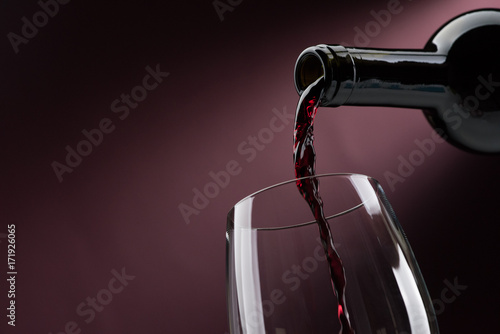 Pouring red wine into a wineglass - 171926065