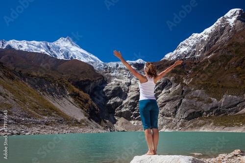 Woman is doing yoga excercises near big lake on the Manaslu circuit trak in Nepala