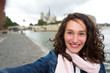 Young woman on holidays in Paris taking selfie in front on Notre Dame - Tourism concept