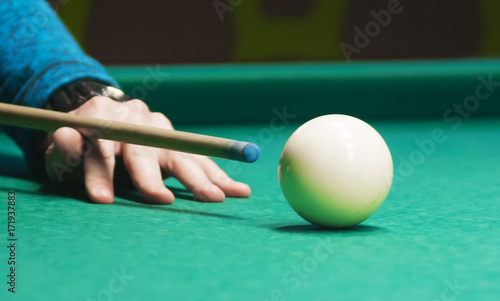 Staande foto Playing billiard. Player hits ball with cue