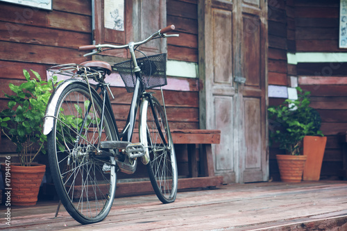 Deurstickers Fiets blue vintage old black and brown bicycle or bike at front of retro wooden home terrace with wood door and window between tree in the flowerpot for exterior and interior decor or classic background