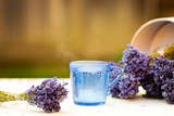 Cup of freshly prepared lavender loose tea in a blue glass cup with dried lavender at the background - 171948473