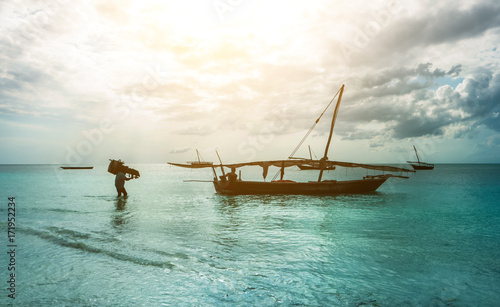 Fotobehang Zanzibar Old rustic fishing boat sitting in the ocean, calm and still turquoise waters, zanzibar