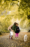 Mother and two girls walking with a dog in the autumn park