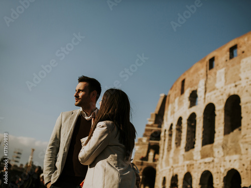 Happy couple hugging in front of Colosseum in Rome, Italy